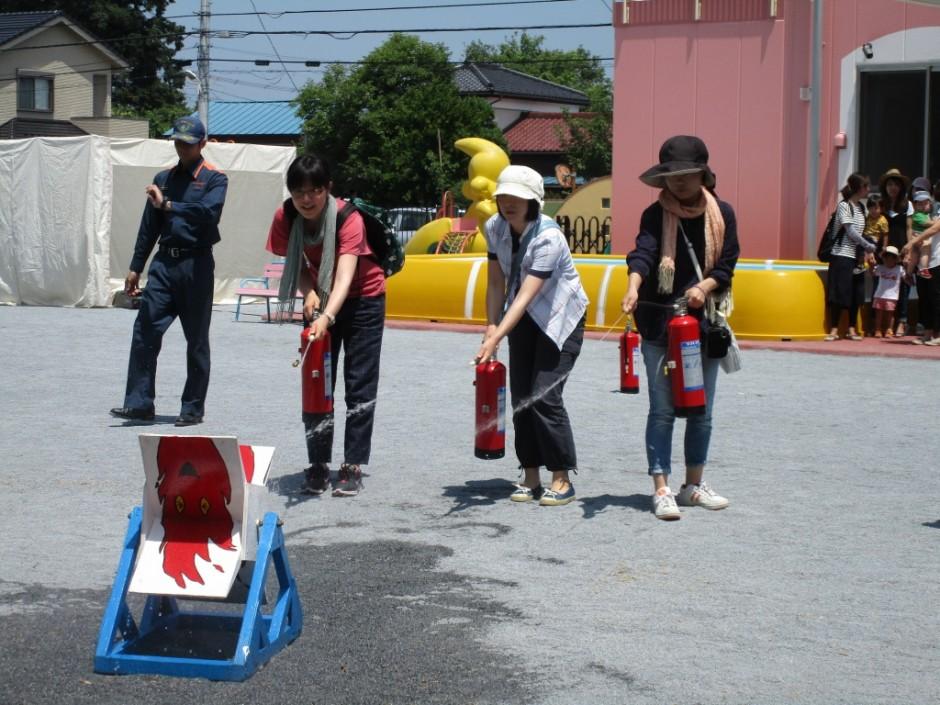 防火講習6月20日 消火器は、炎の根元から掃くように消火いたします。参加したお母さんも頑張りました。