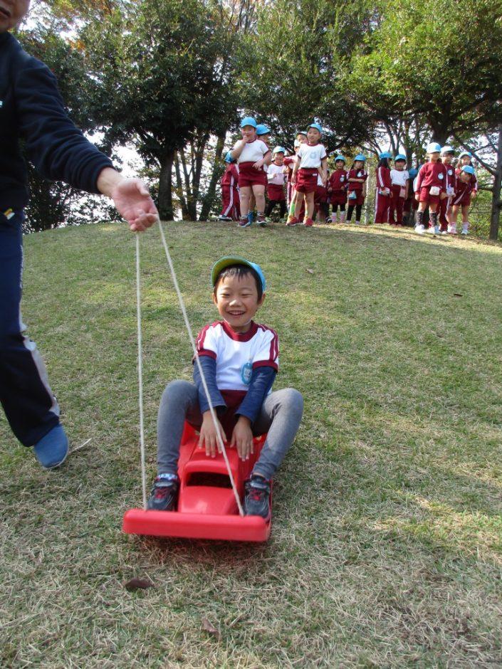 園外保育(年中・年少) 秋空の下、みんなで元気にそり遊び♪いい笑顔(^^)