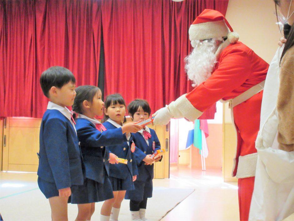 幼稚園部 クリスマス会 サンタクロースからプレゼントがありました! みんなサンタさんのお顔じっとみています☆彡